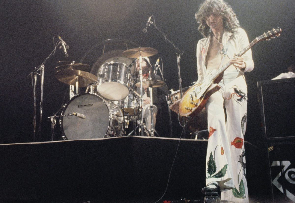 A view of John Bonham on drums with Jimmy Page playing guitar in a white suit with red poppies and other colorful objects on it in 1977