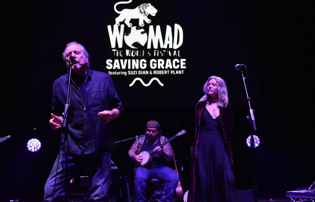 Robert Plant sings with Suzi Dian standing to his left and a member of Saving Grace performing on banjo behind them