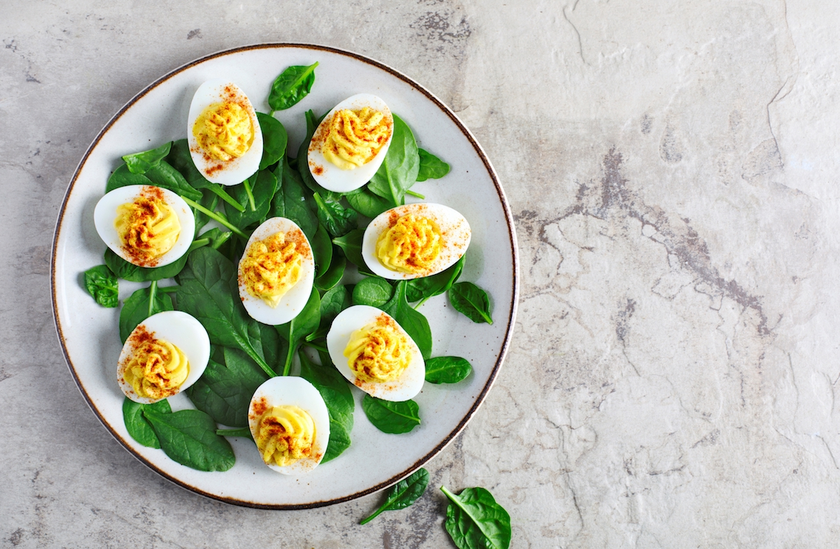 Plate of deviled eggs with spinach on a marbled background