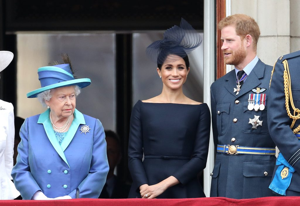 Queen Elizabeth II, Prince Harry, and Meghan Markle on the balcony of Buckingham Palace for the Centenary of the RAF on July 10, 2018