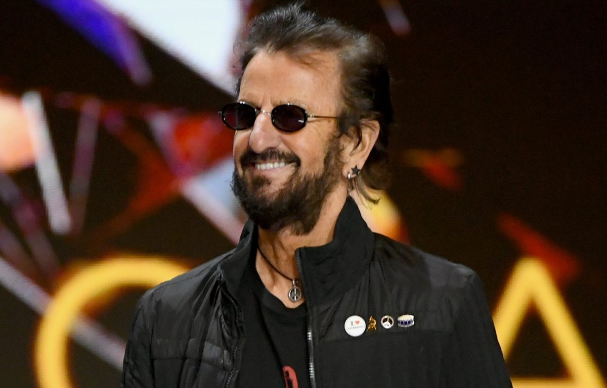 Ringo Starr, wearing sunglasses, smiles during a presentation at the 2021 Grammys
