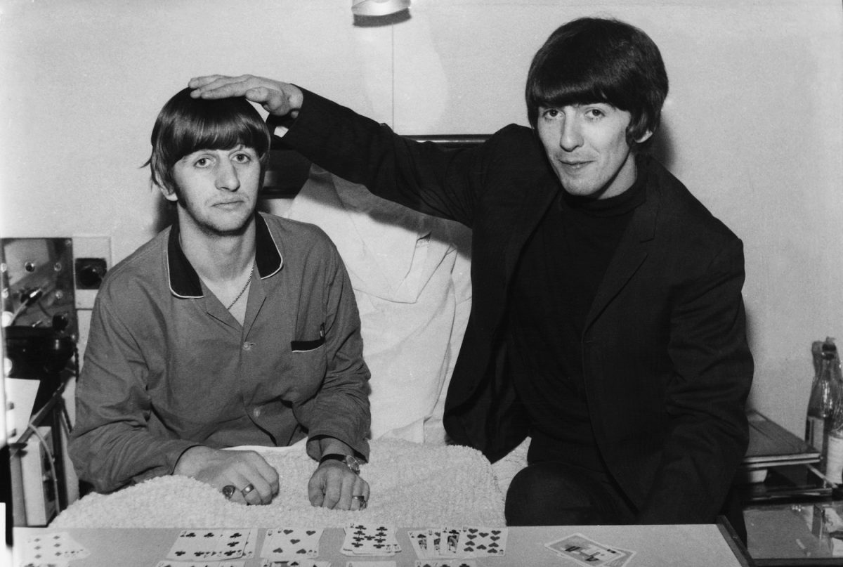 A smiling George Harrison holds his hand on top of Ringo Starr's head as the two sit in a hospital bed in 1964