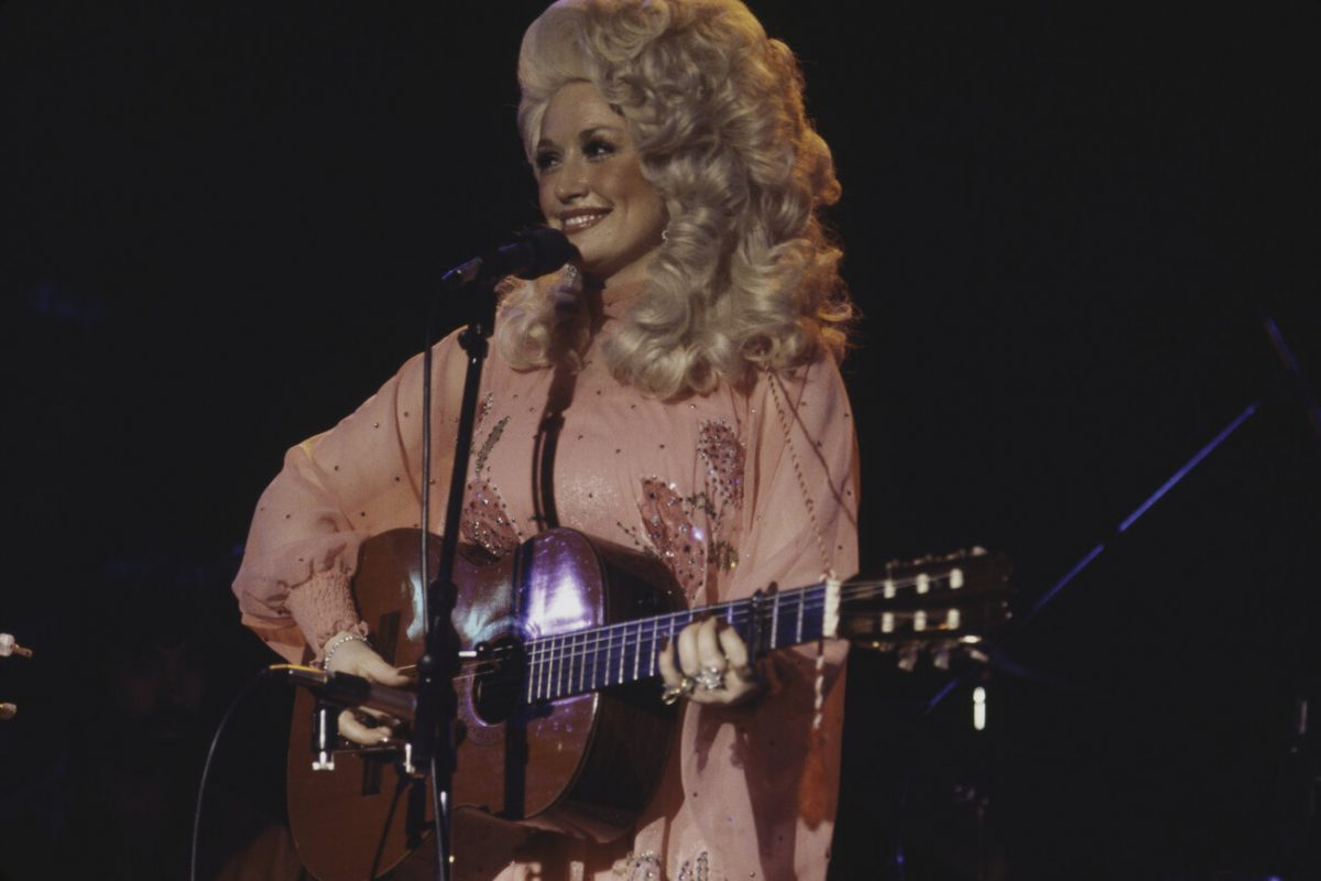 Dolly Parton performing on stage in New York in 1977. She's wearing a pink dress and big, blond, curly hair.