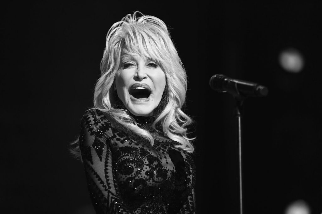 A black and white close-up of Dolly Parton singing into a microphone.