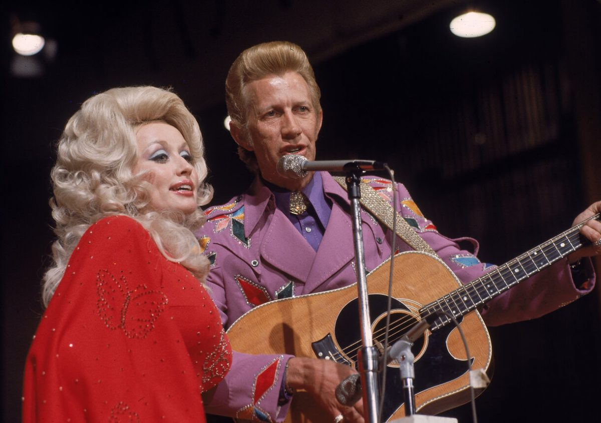 Dolly Parton and Porter Wagoner singing on stage in Nashville in 1978. Parton is in a bright red shirt with her hair in a beehive. Wagoner is in a purple jacket strumming a guitar.