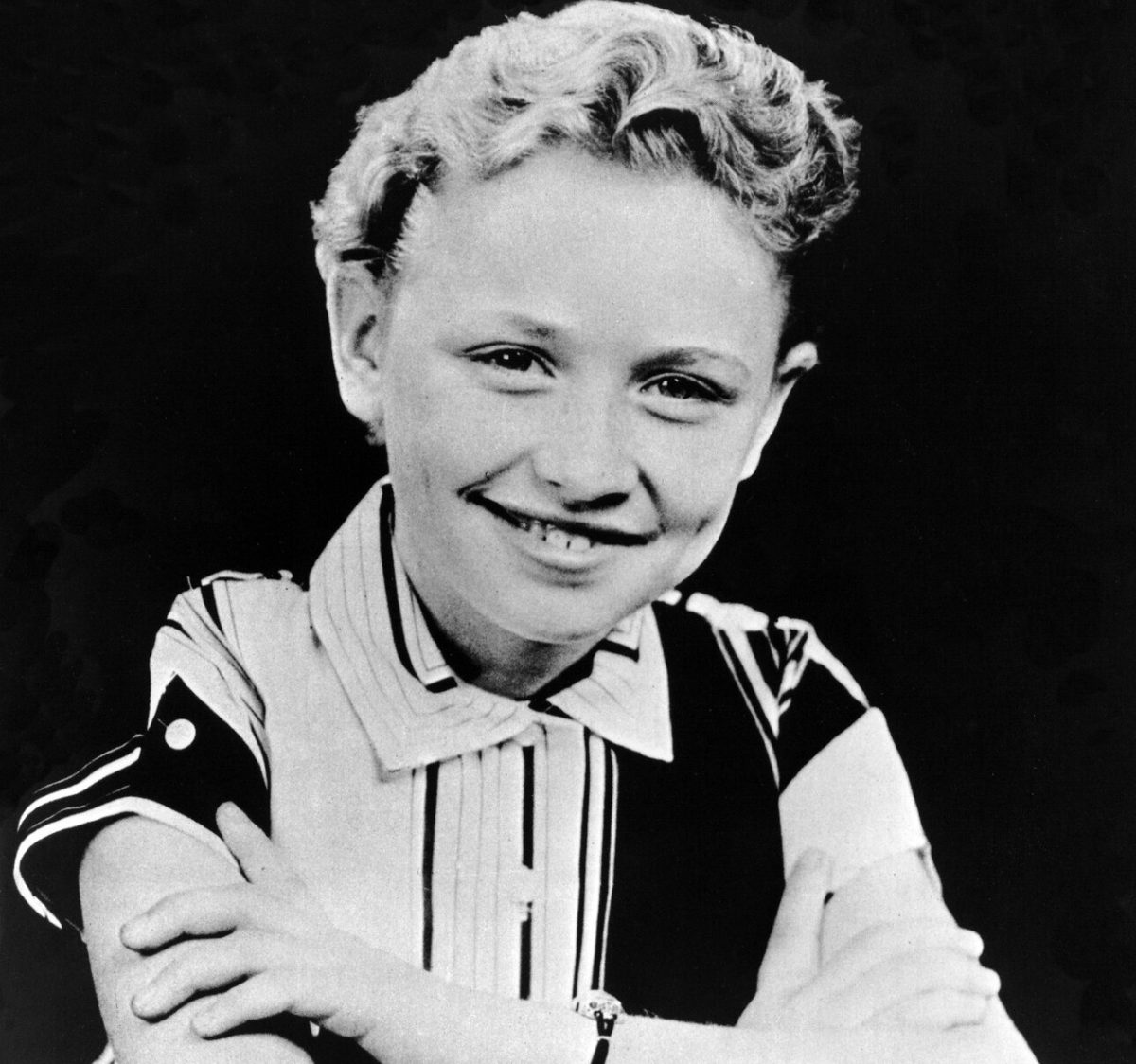 Dolly Parton poses for a portrait as a child in 1955. The photo is black and white. She wears short hair and a collared shirt.
