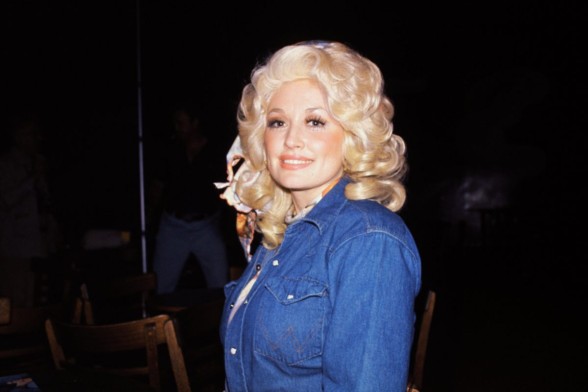 Dolly Parton in a jean shirt with big, curly blond hair.