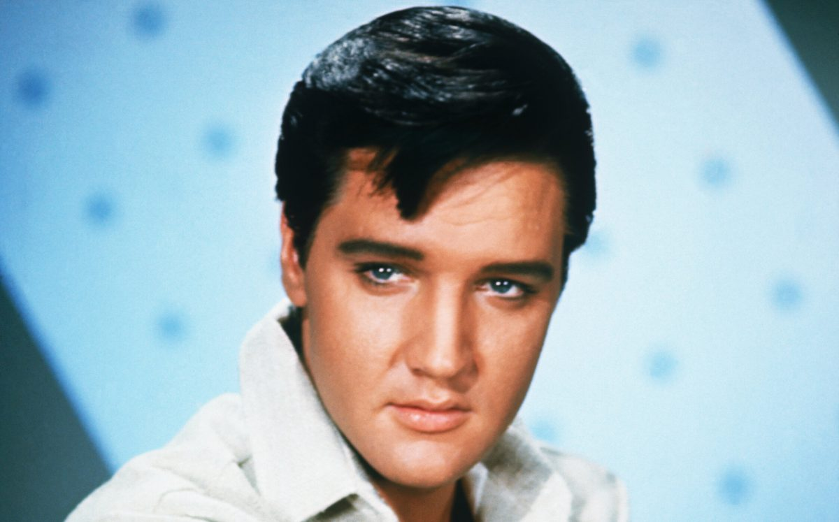 A close-up of Elvis Presley. He's in a white shirt in front of a light blue background.