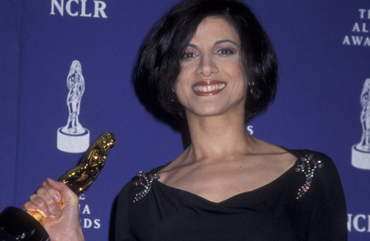 Saundra Santiago smiling and holding an award statuette in 2001
