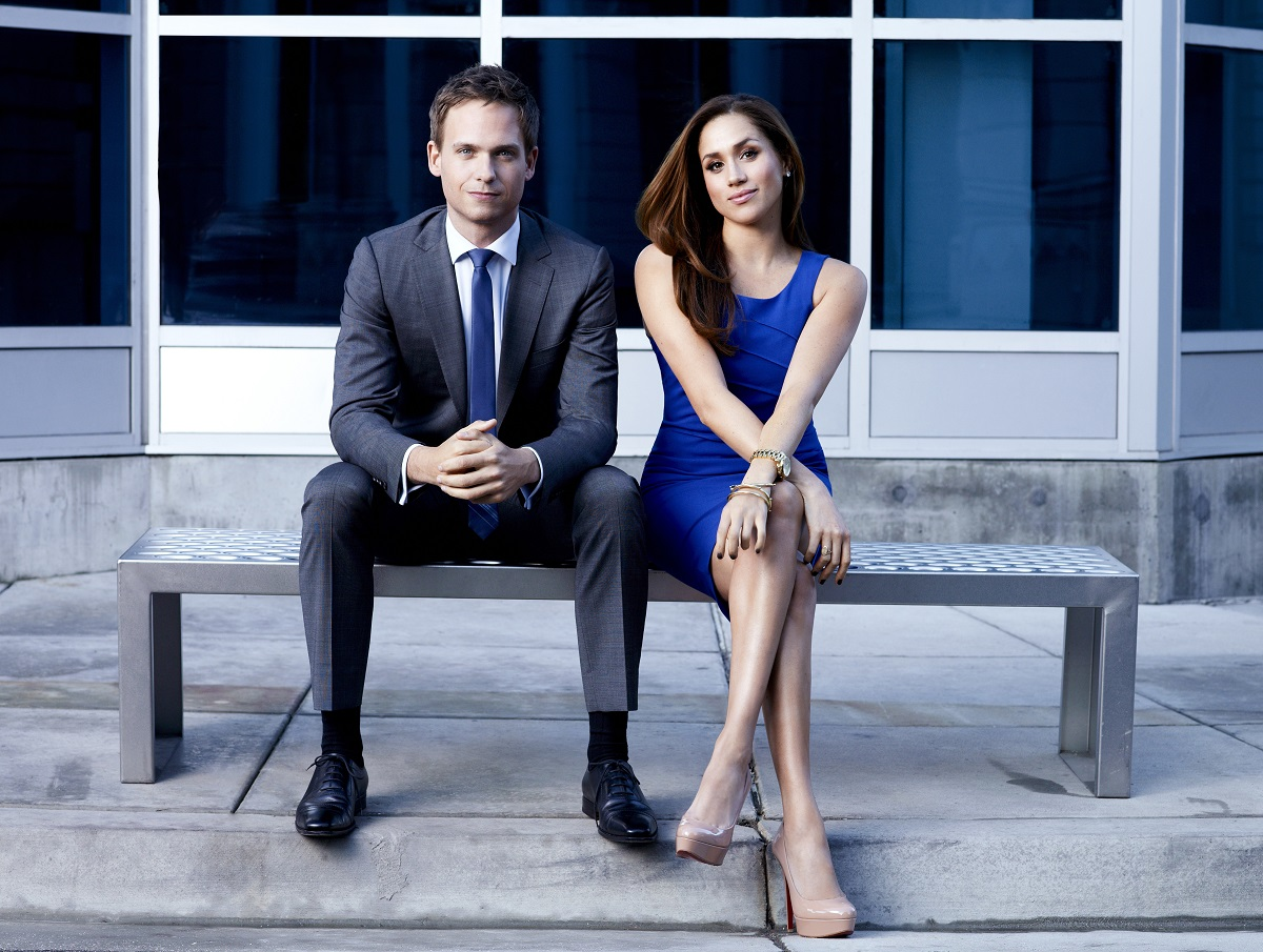 Patrick J. Adams and Meghan Markle sitting on a bench in a promo shoot for 'Suits'