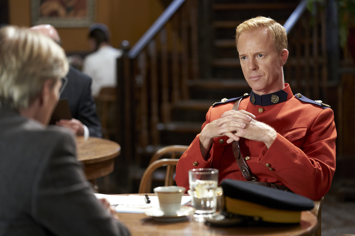 Superintendent Hargraves sitting opposite Bill at a table