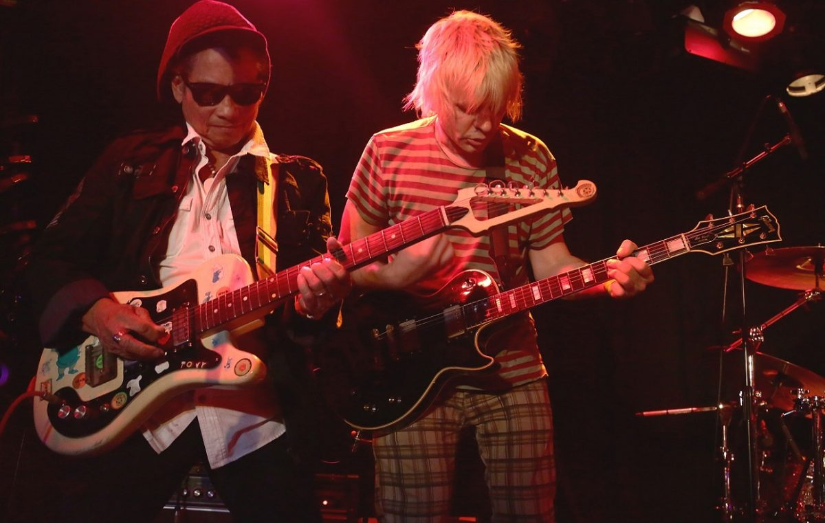 Tony Chin and Zak Starkey playing guitar on stage in 2016