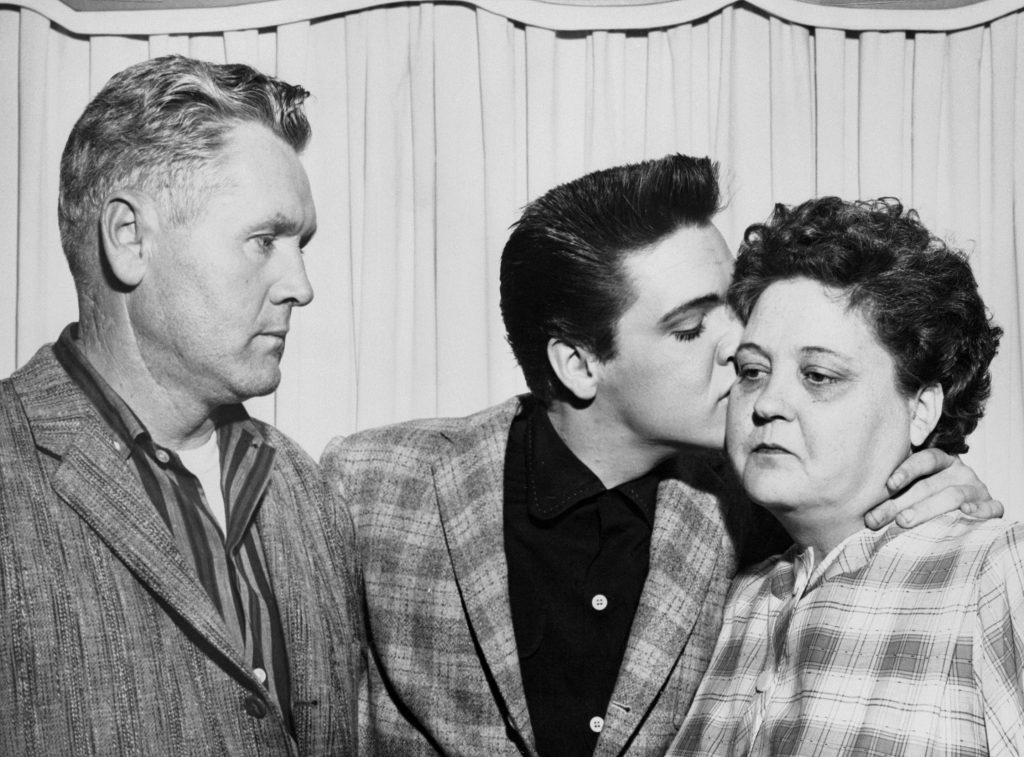 Vernon, Elvis, and Gladys Presley near curtains