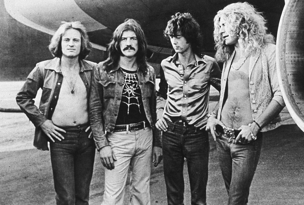 Led Zeppelin posing in front of the engine of the band's private plane