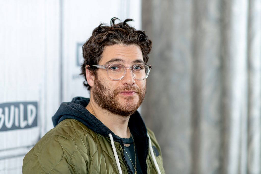 Adam Pally smiling in front of a gray background