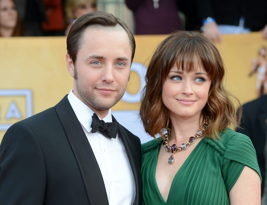 (L-R) Vincent Kartheiser and Alexis Bledel smiling in front of a blurred crowd
