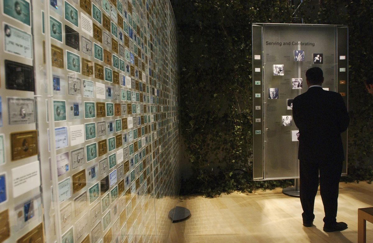 An unidentified guest looks at a wall of American Express cards at the 'Annie Leibovitz: Rewarding Lives exhibition' in West Hollywood in 2004