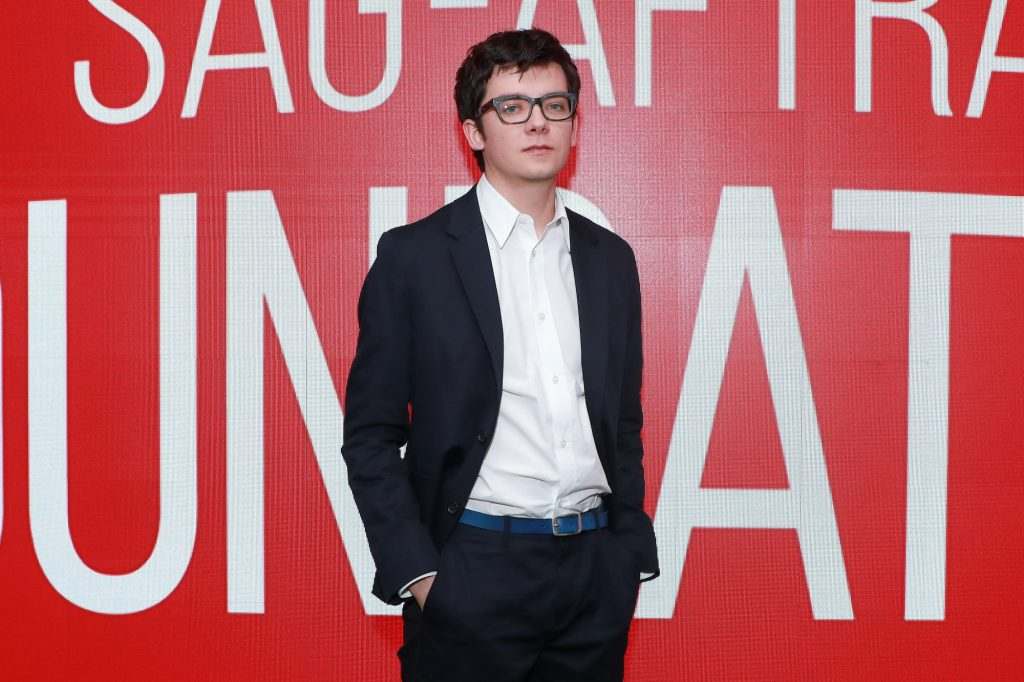 Asa Butterfield in front of a red background