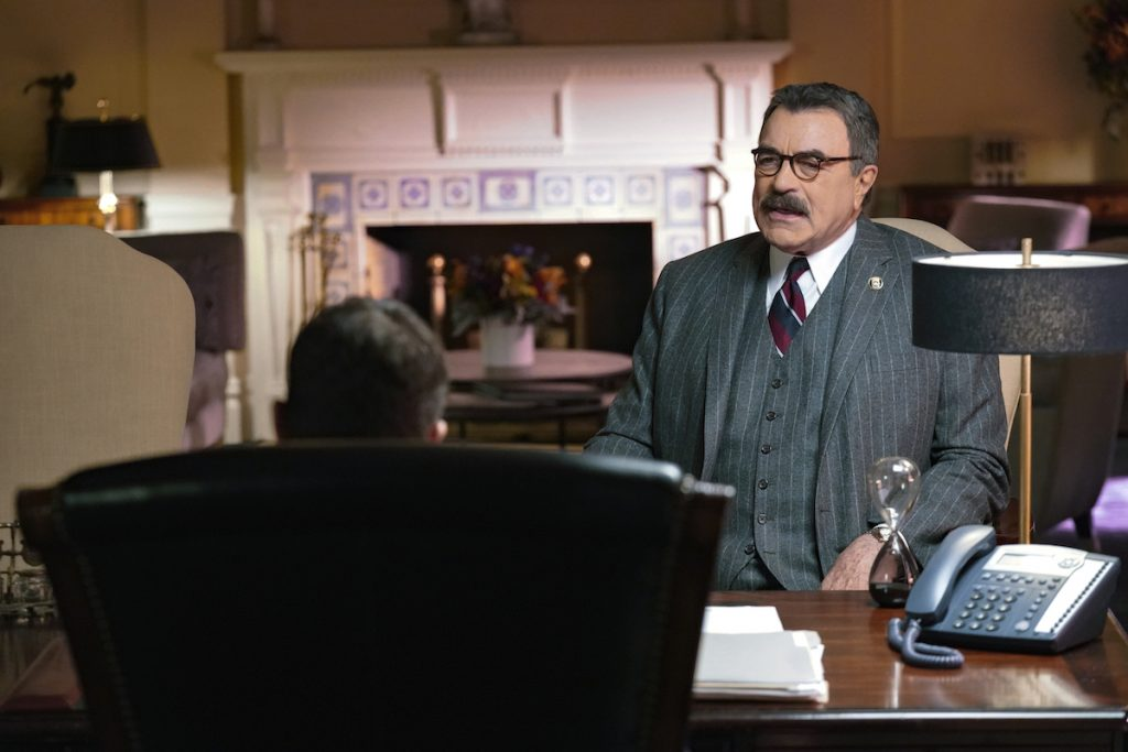 Tom Selleck as Frank Reagan sits in a chair talking to someone in an office on 'Blue Bloods'