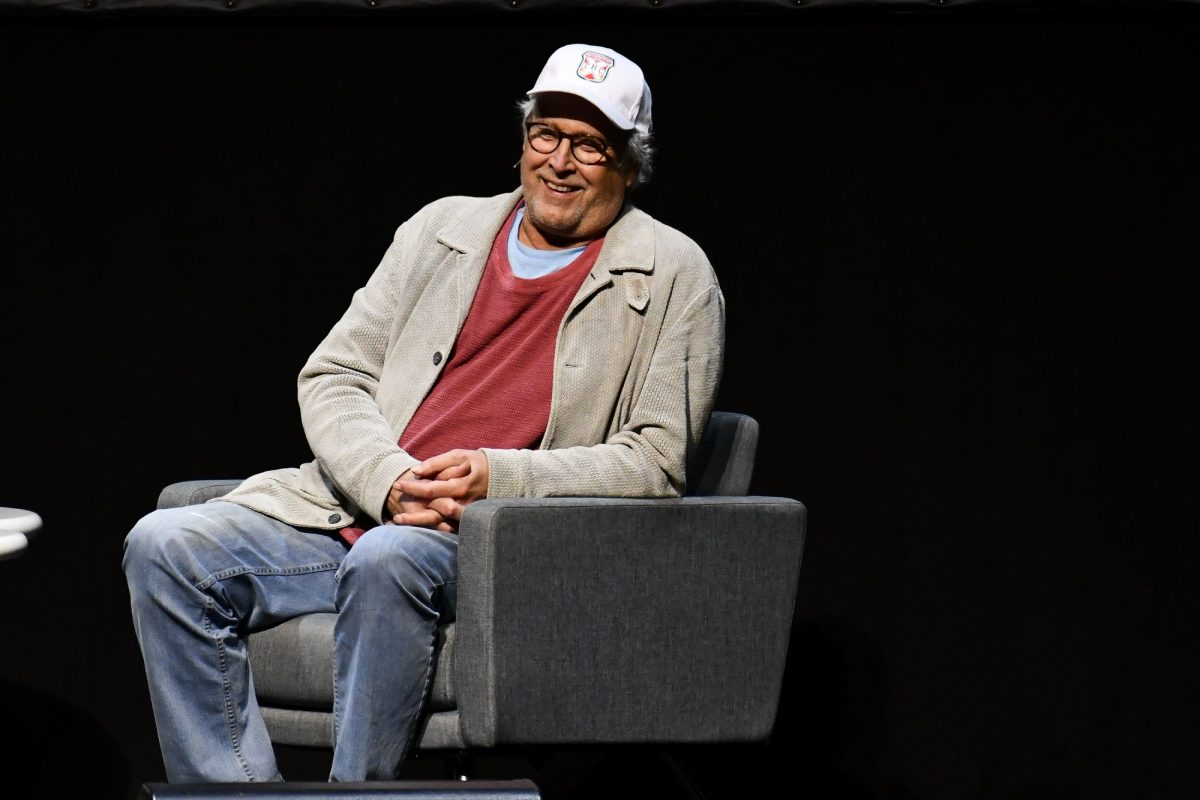 Chevy Chase sitting in a chair for a Q&A
