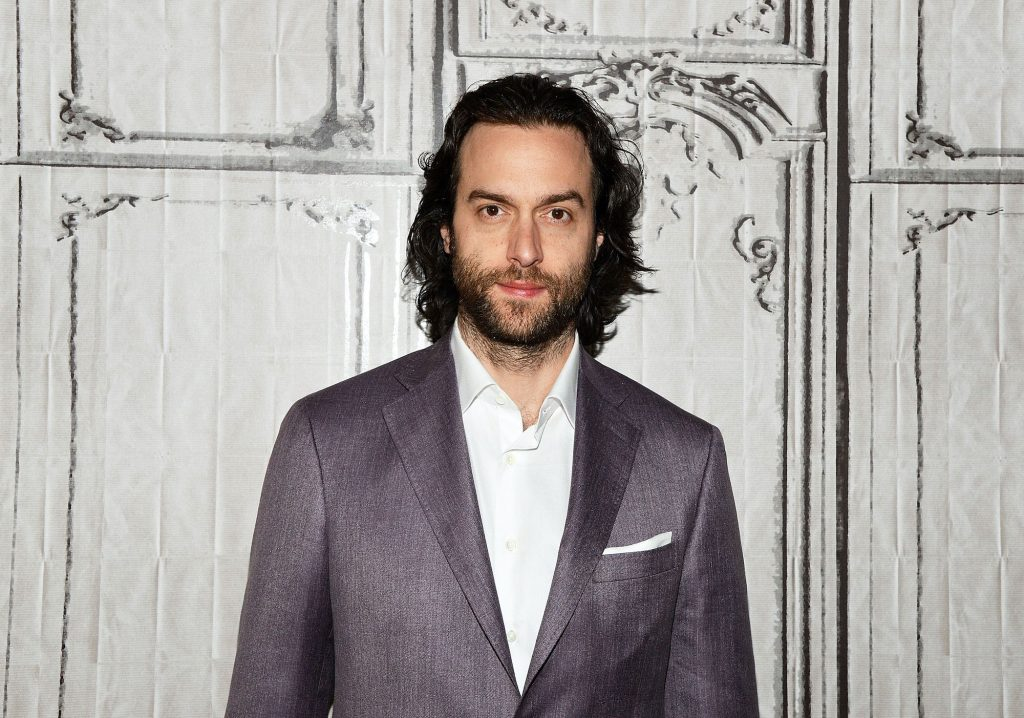 Chris D'Elia smiling in front of a white background