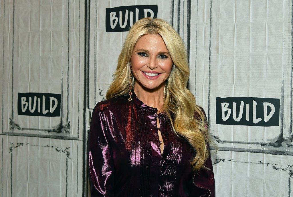 Christie Brinkley smiling in front of a white background