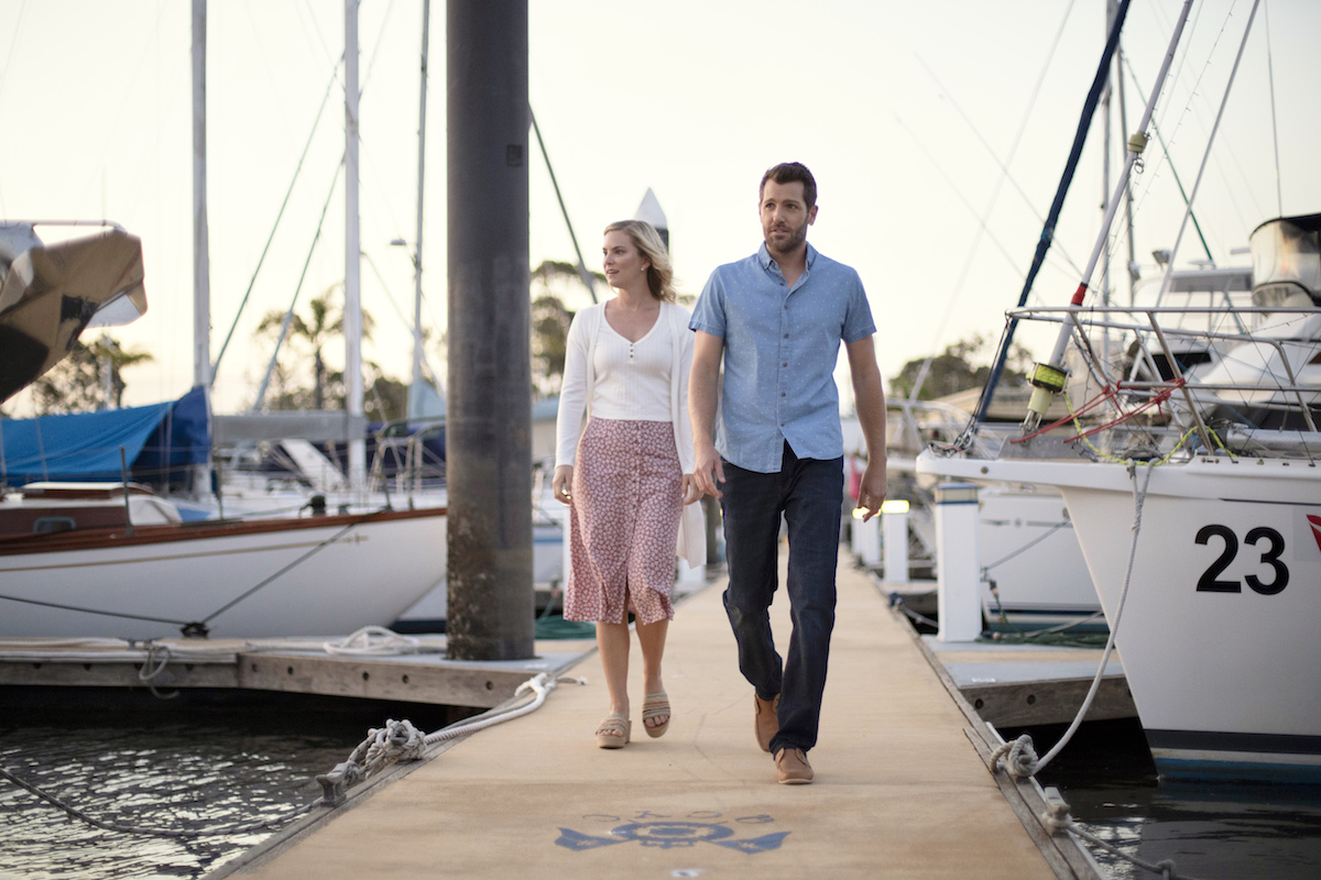 Cindy Busby and Tim Ross walk on a pier in a scene from Hearts Down Under
