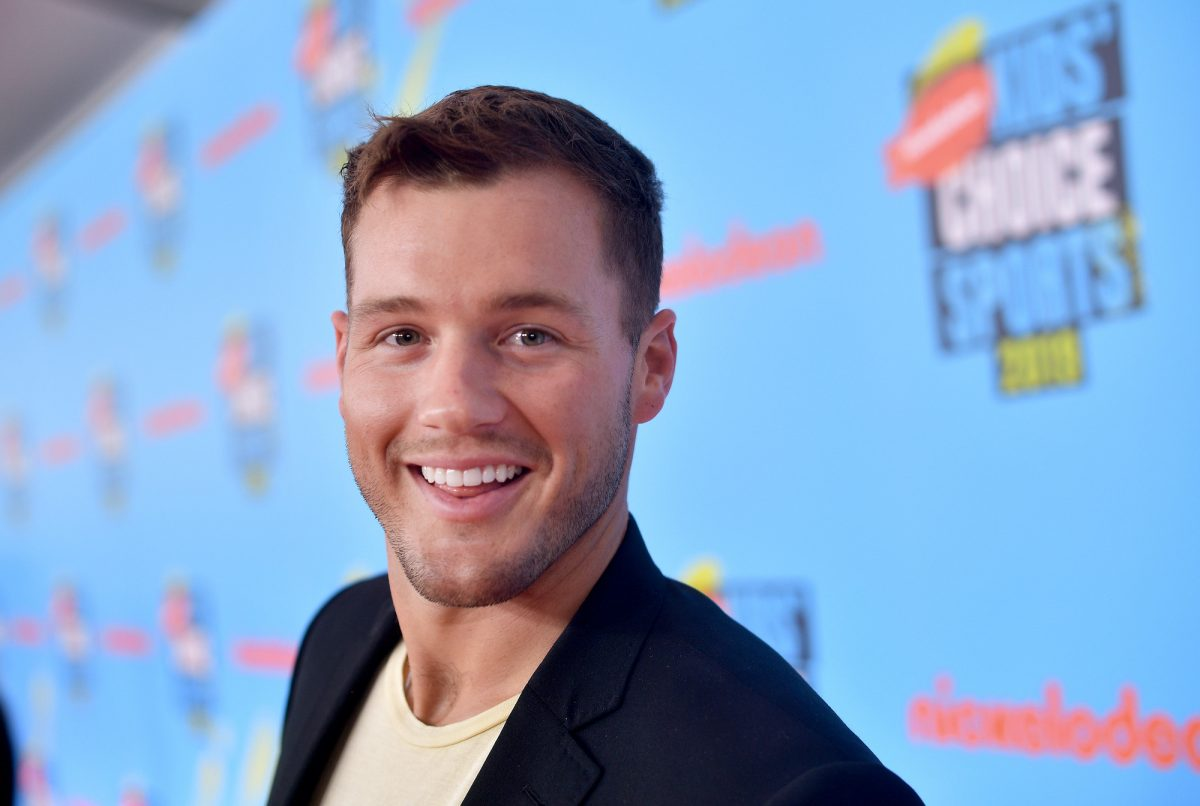 Colton Underwood smiling in front of a blue background