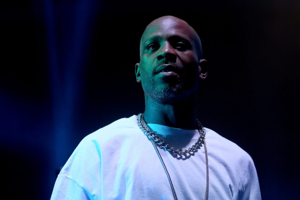 DMX performs on stage cast in blue and green light