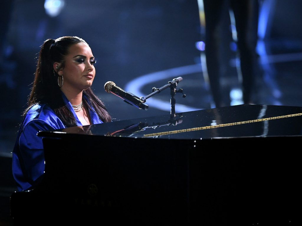 Demi Lovato sits at a piano ready to sing