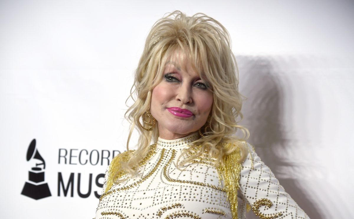A close-up of Dolly Parton in a white and gold dress at the 2019 MusiCares Person Of The Year Honoring Dolly Parton