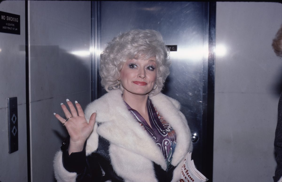 Dolly Parton waves to the camera in a fur coat.
