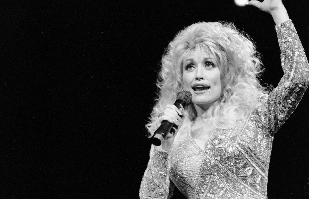 Dolly Parton performing in black and white.
