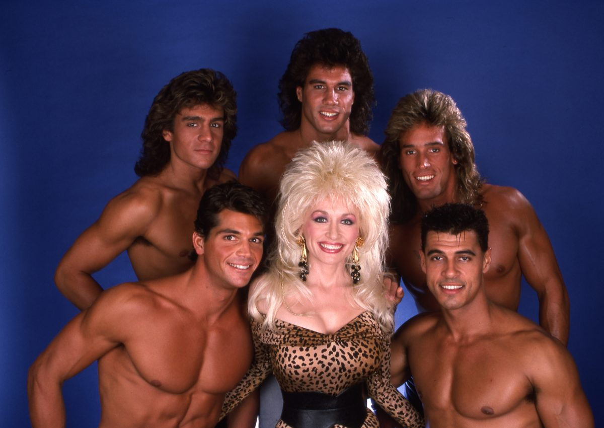 Dolly Parton and The Chippendales. Parton is in a leopard top with her signature big hair.