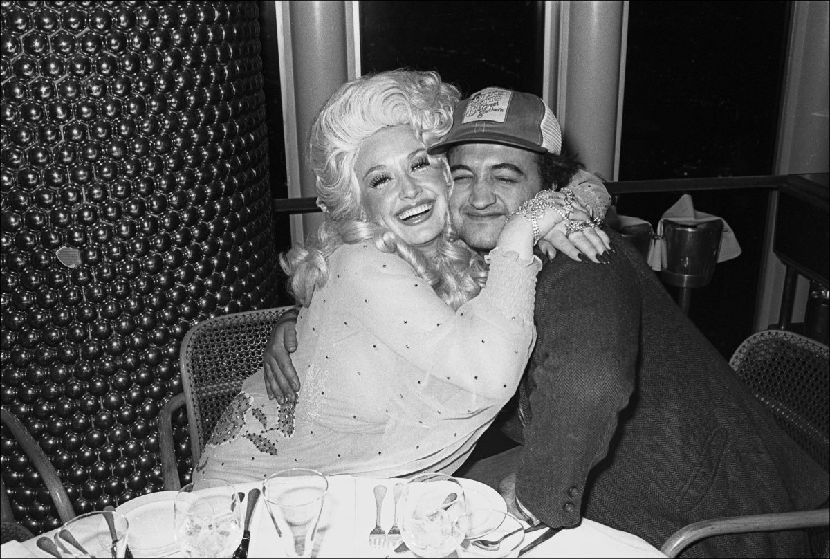 Dolly Parton and comedian John Belushi hug as they pose together at the Windows on the World restaurant.