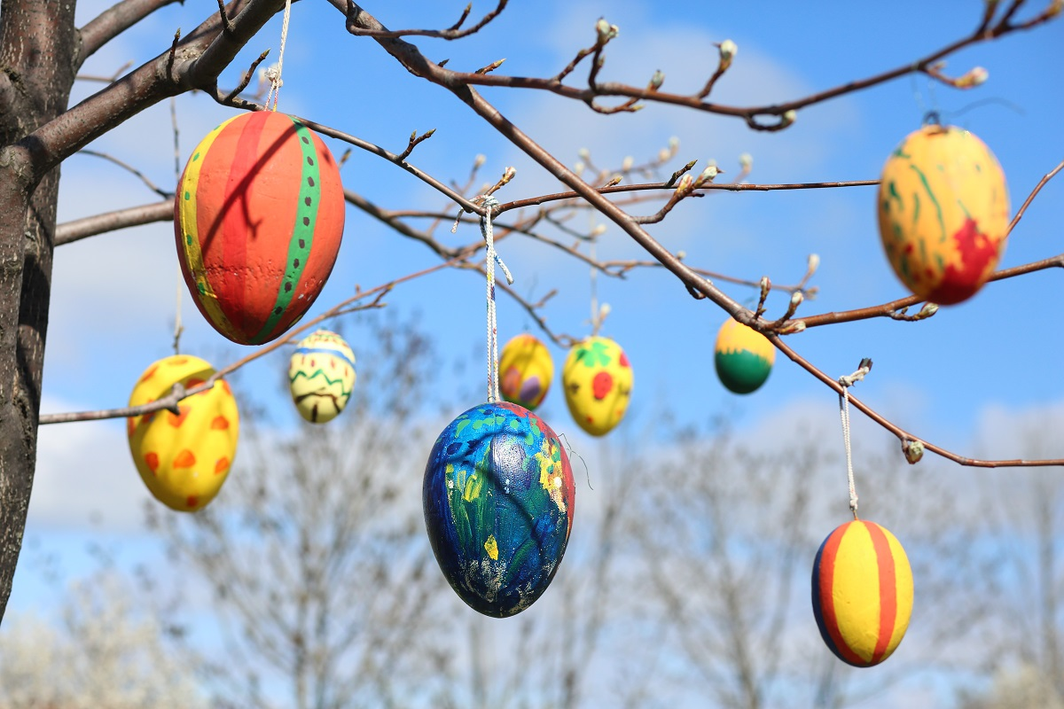 """Painted Easter eggs hang on a tree in the miniature park """"Kleiner Harz""""."""