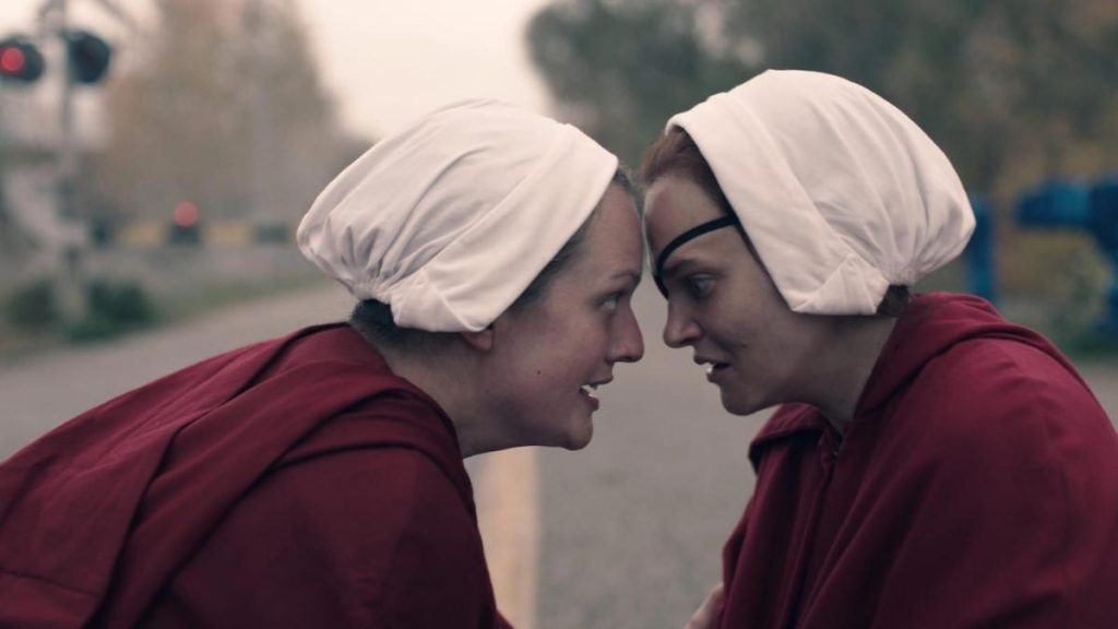Elisabeth Moss as June Osborne and Madeline Brewer as Janine in red Handmaids robes and white bonnets in 'The Handmaid's Tale' Season 4 Episode 4, 'Milk'