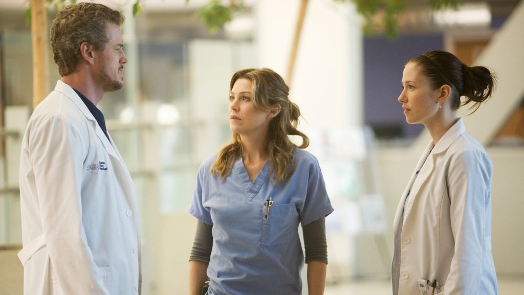 Eric Dane as Mark Sloan, Ellen Pompeo as Meredith Grey, and Chyler Leigh as Lexie Grey looking at each other in 'Grey's Anatomy'