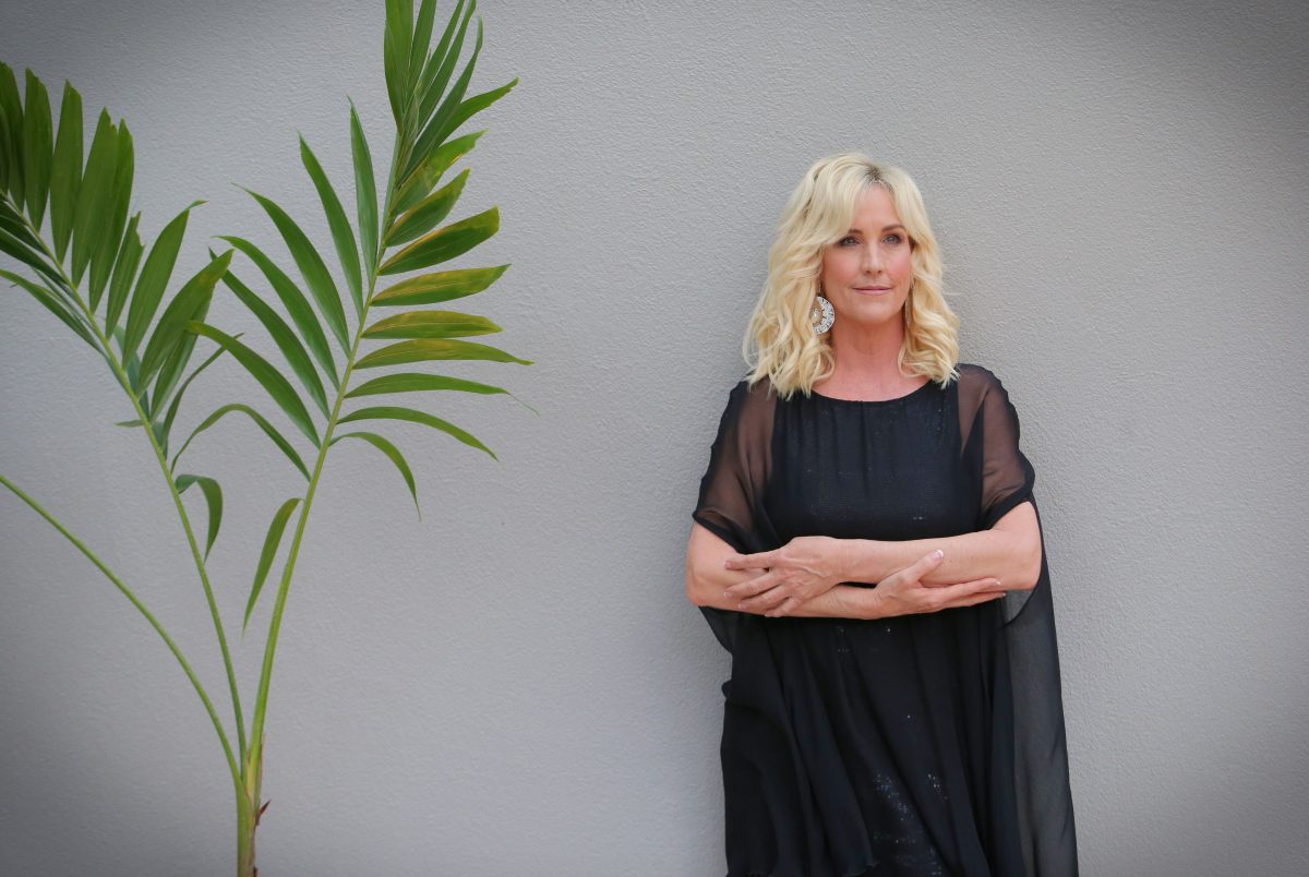 Activist Erin Brokovich in a black dress standing against a gray wall