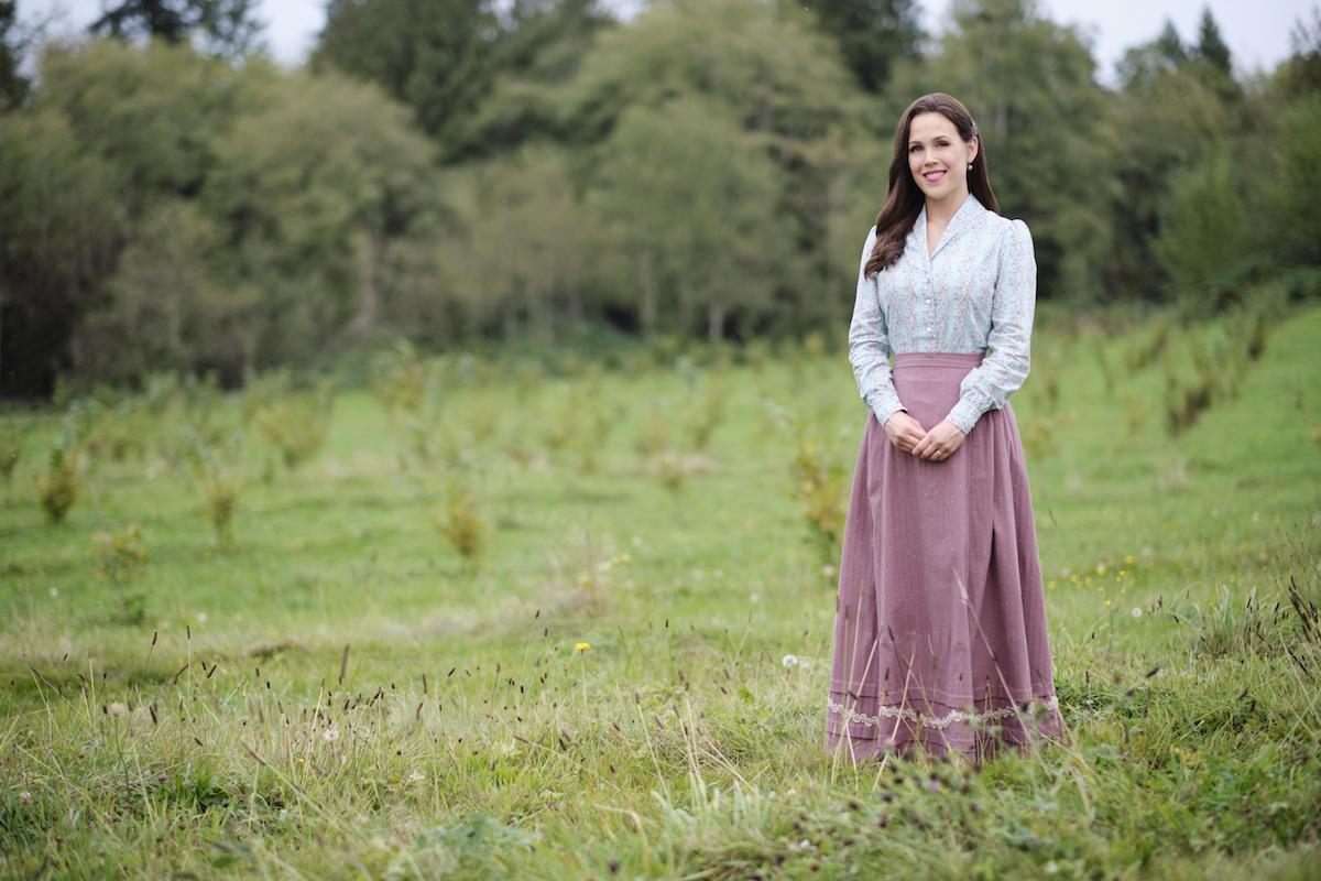 Elizabeth standing in a field on When Calls the Heart