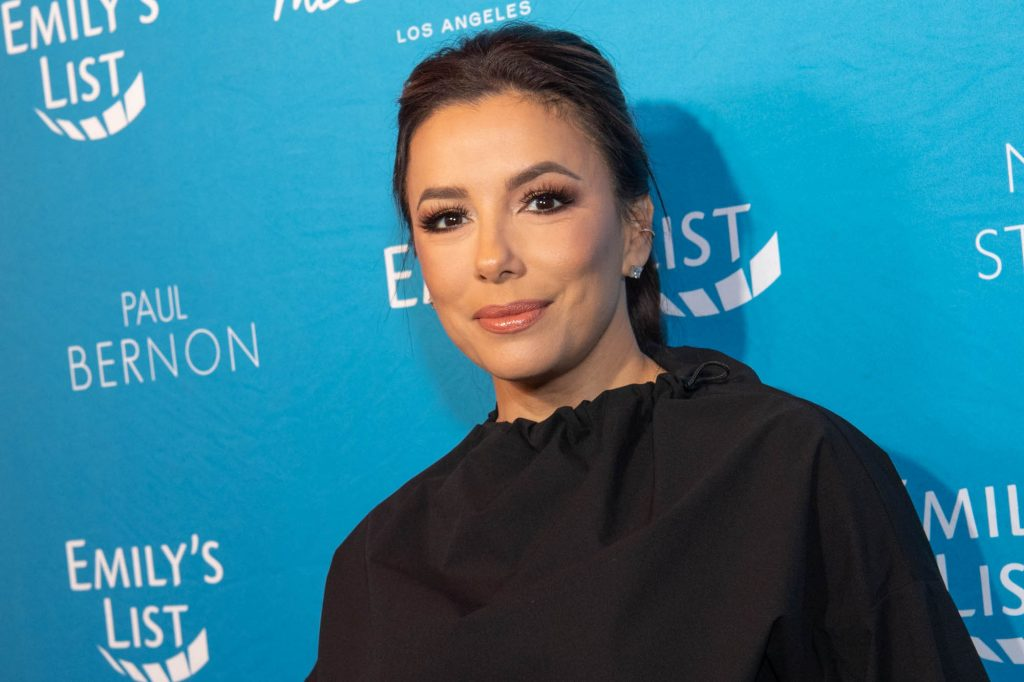 Eva Longoria smiling in front of a blue background