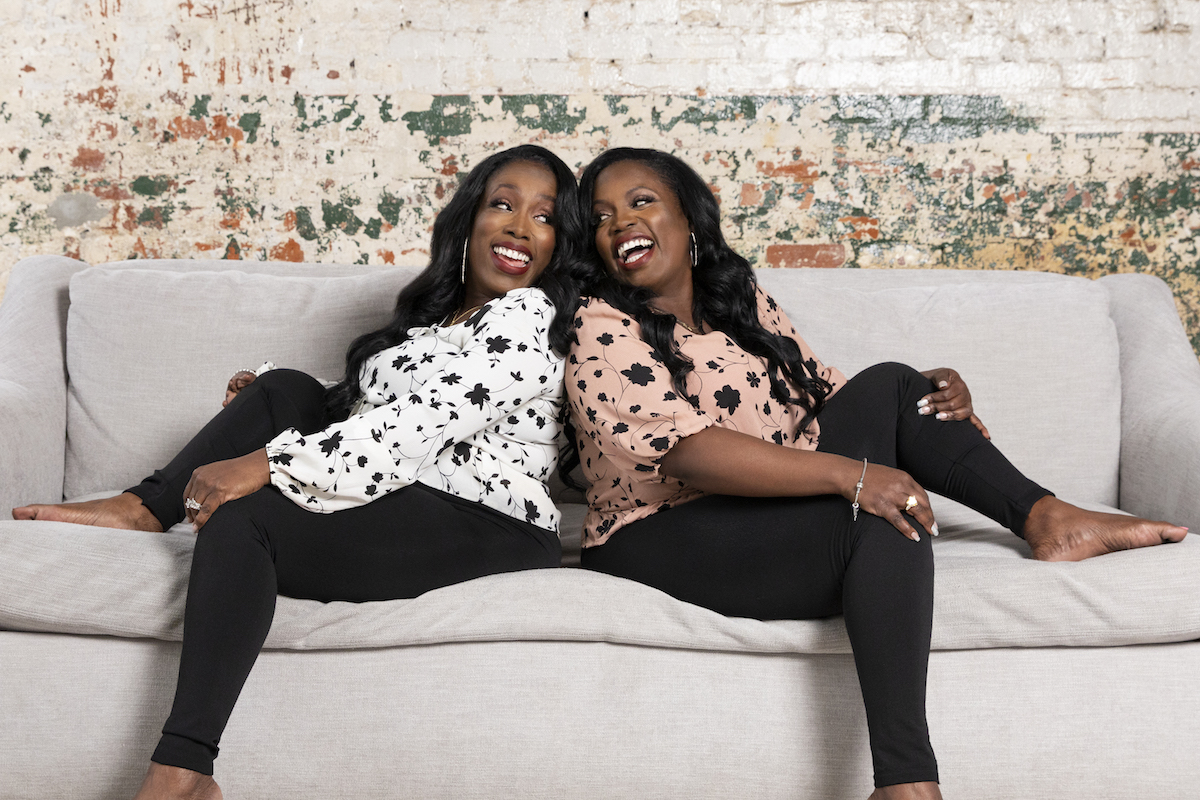 Patrix and Patrica from Extreme Sisters sitting on a couch