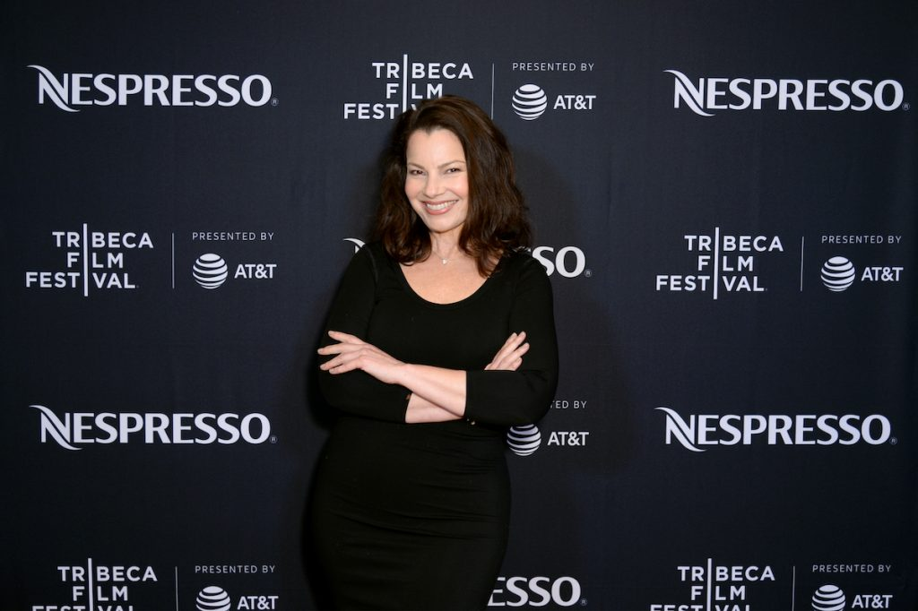 Fran Drescher smiles with her arms folded on the red carpet