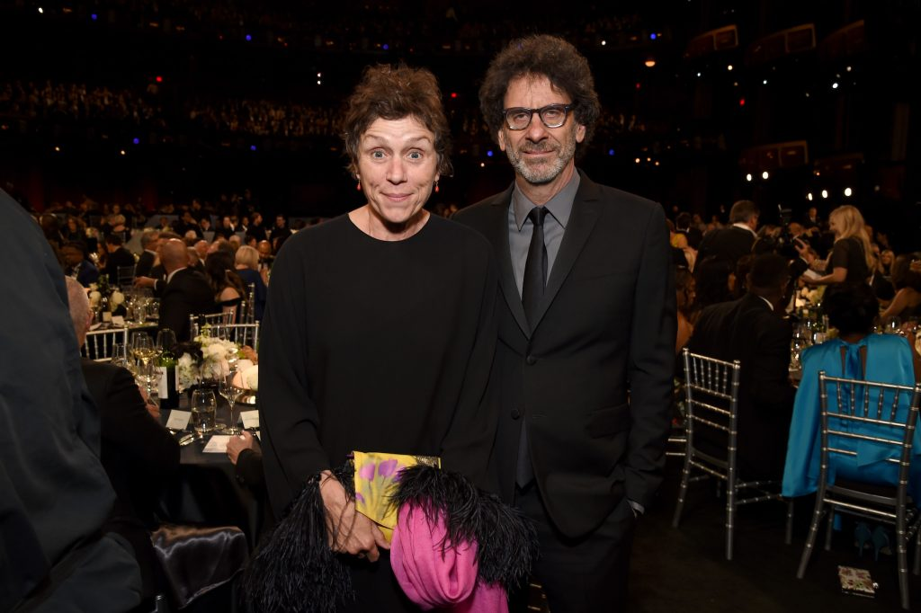 (L-R) Frances McDormand and husband Joel Coen standing together and looking at the camera