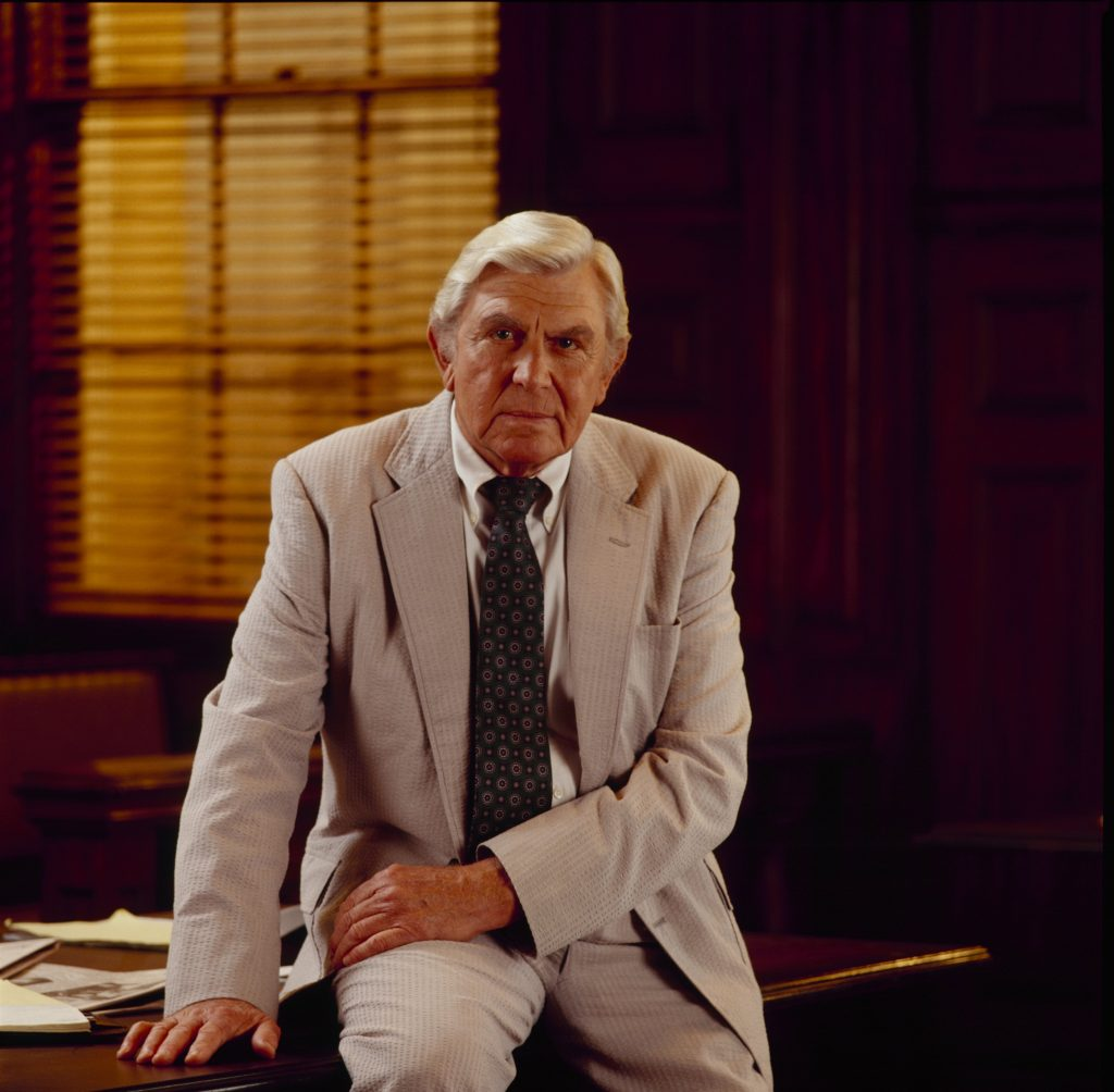 Andy Griffith is photographed seated on the edge of a desk in a light-colored suit as Ben Matlock, lead character of the legal drama 'Matlock,' 1992