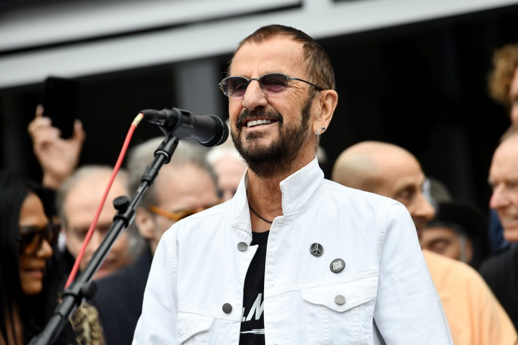Former Beatle Ringo Starr smiles as he greets a crowd wearing a white jacket and his trademark violet sunglasses.