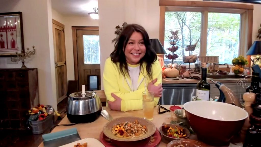 Rachael Ray poses during Food Network's 'In the Kitchen With Rachael Ray' in a sunny yellow sweater, while leaning on her kitchen counter.