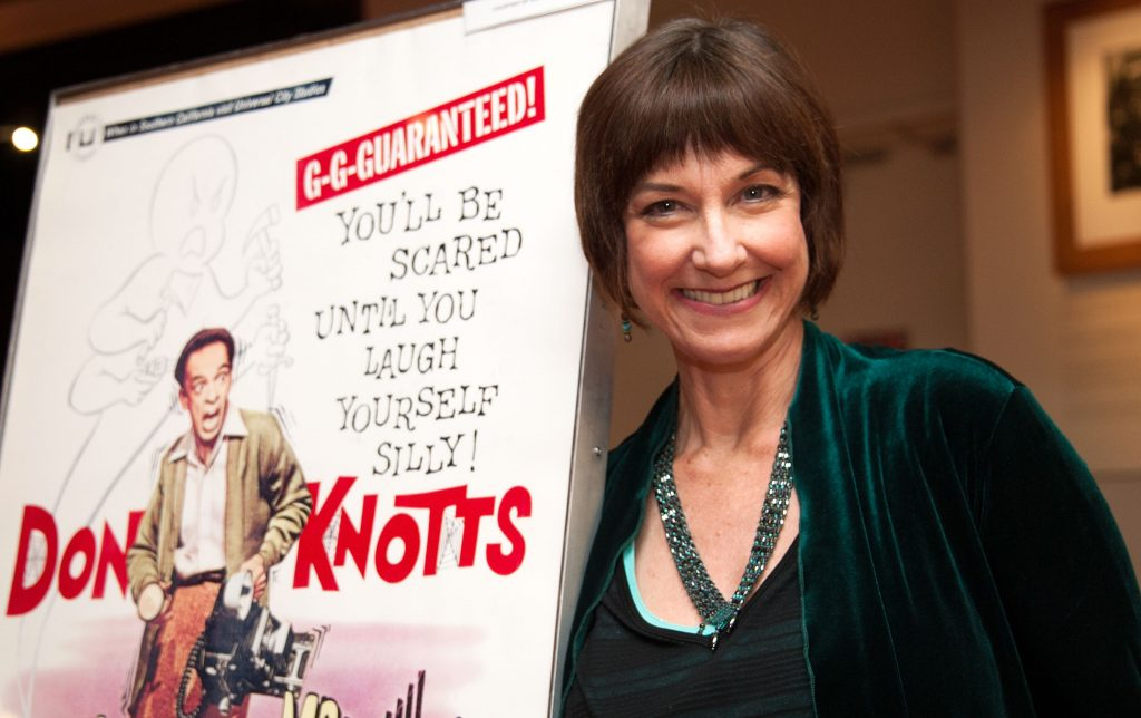 Actor Karen Knotts, daughter of Don Knotts, poses in front of a promotional poster for her father's 1966 film, 'The Ghost and Mr. Chicken', 2012