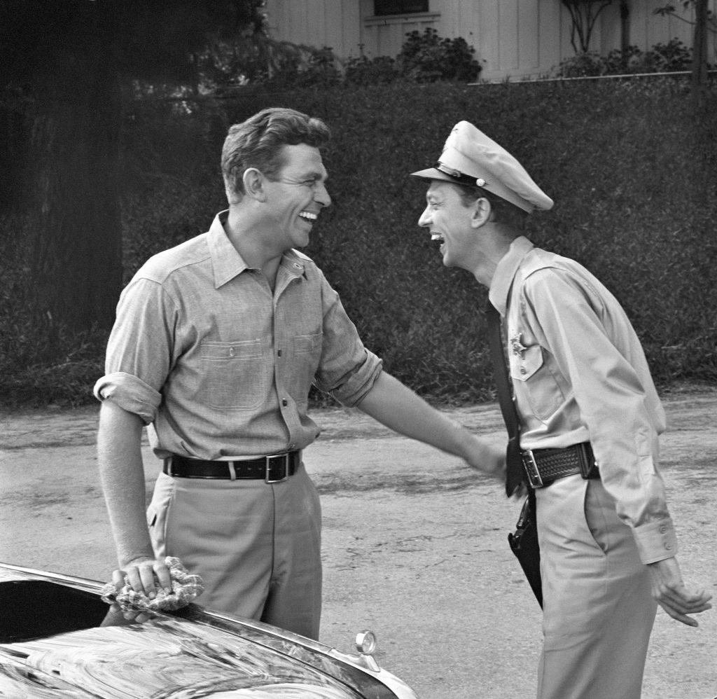 Andy Griffith and Don Knotts laugh together in a scene from the first episode of 'The Andy Griffith Show,' 1960