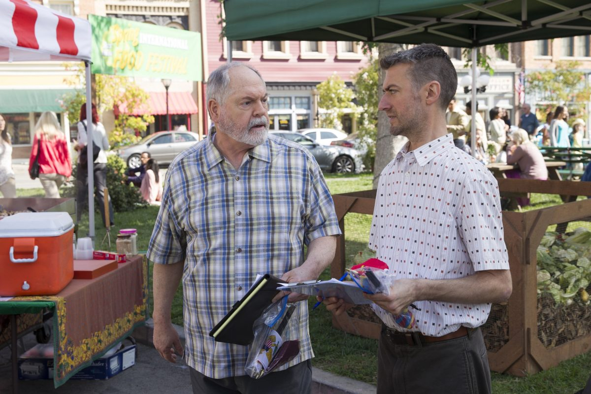 Michael Winters as Taylor Doosey and Sean Gunn as Kirk Gleason discuss town business in Stars Hollow's town center